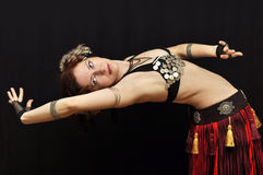 Dancer bend. Dancer in fancy tribal skirt bending back isolated on black Royalty Free Stock Photo