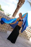 Dancer in black. Pretty and fit blonde belly dancer in black skirt with silk veil dancing outside on balcony Royalty Free Stock Photography