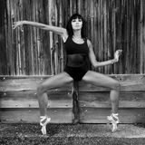 Dancer with dance shoes against a wooden door. Beautiful woman dancing outdoors against a wooden door. She wears dance shoes and black leotard. She is on Stock Image