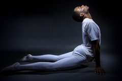 Dancer Demonstrating Flexibility. Black male dancer practicing warm up exercises for flexibility Royalty Free Stock Images