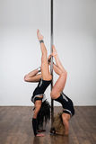 Dancer doing difficult acrobatic tricks with a pole Royalty Free Stock Images