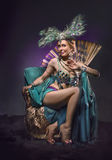 Dancer in exotic costume sits in armchair Royalty Free Stock Images