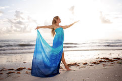 Dancer in goddess like pose. A female dancer is posing in profile with arms raised and looking at her open hand at the beach with brightness of the sun diffusing Stock Photo