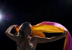 Dancer with headscarf. Dancer waving a colorful oriental headscarf, backlit studio shot Stock Photo