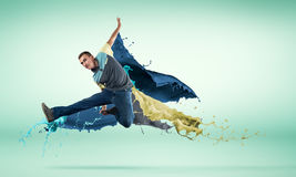Dancer in jump. Young male dancer in jump on white background with colorful paint plashes Royalty Free Stock Photo
