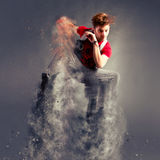 Dancer jumping from explosion. Young modern dancer jumping high from explosion royalty free stock photography