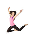 Dancer Jumping and Laughing. Full body portrait of asian american dancer jumping in studio on white background wearing casual athletic clothing (pink Stock Photo