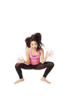 Dancer Jumping and Laughing. Full body portrait of asian american dancer jumping in studio on white background wearing casual athletic clothing (pink Royalty Free Stock Images