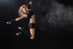 Dancer jumping while performing her dance routine. Contemporary dancer woman jumping dance on black background Royalty Free Stock Photography