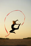 Dancer jumping with ribbon. Professional gymnast woman dancer jumping with ribbon stock photography