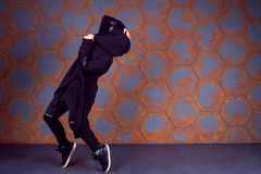 Dancer in motion. Young dancer standing on his tiptoes near the wall. Urban style Stock Photo