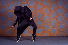 Dancer in motion. Young dancer standing on his tiptoes near the wall. Urban style Stock Photography