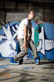 Dancer performing dance move in front of wall. Dancer performing dance move in front of graffiti wall Stock Photography