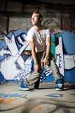 Dancer performing dance move in front of wall. Dancer performing dance move in front of graffiti wall Stock Image