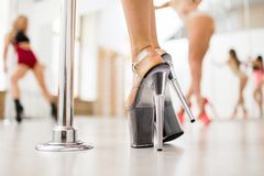 Dancer by pole. Feet of contemporary young poledancer in high-heeled shoes during exercise by pole stock image