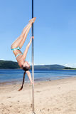 Dancer on pole makes acrobatic sketch. Summer beach stock photos
