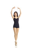 Dancer Posing en Pointe. Full body portrait of asian american dancer posing en Pointe in studio on white background wearing classic ballet clothing (black Royalty Free Stock Photo