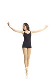 Dancer Posing en Pointe (hands out). Full body portrait of asian american dancer posing en Pointe in studio on white background wearing classic ballet clothing ( Royalty Free Stock Images