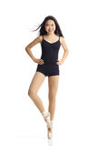 Dancer Posing en Pointe Looking at Camera. Full body portrait of asian american dancer posing en Pointe in studio on white background wearing classic ballet Royalty Free Stock Image