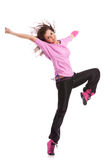 Dancer posing with leg raised. Young and beautiful woman modern dancer posing with leg raised and hands extended, smiling at the camera Royalty Free Stock Image
