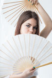 Dancer posing with a pair of fan. Model or dancer posing and hiding behind a couple of fan Royalty Free Stock Images