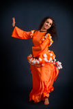 Dancer posing in traditional orange costume Stock Photo