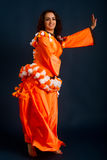 Dancer posing in traditional orange costume Stock Photography