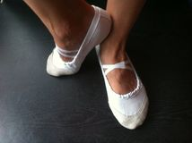 The dancer`s legs in ballet flats stock image