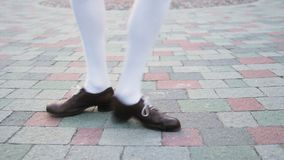 Dancer`s legs close-up, loop. Girl dancing solo jazz swing dance. Funny dance on the city`s square pavement. stock video
