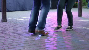 Dancer's legs perform lindy hop dance step on the city's square pavement. Street music day. Dancer's legs perform lindy hop dance step on the stock video footage