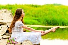 Dancer sits on a bridge and pulling sock feet Stock Photo