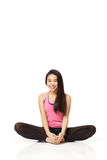 Dancer Sitting. Full body portrait of asian american dancer sitting casually in studio on white background wearing casual athletic clothing (pink Royalty Free Stock Photography