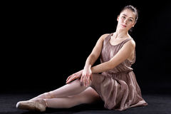 Dancer sitting with grace. Ballet dancer sitting with grace on a stage Stock Images