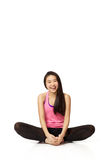 Dancer Sitting and Laughing. Full body portrait of asian american dancer sitting casually in studio on white background wearing casual athletic clothing (pink Stock Images