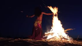 Dancer in special clothes is dancing belly dancing, near the fire