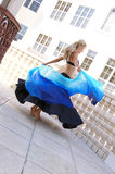 Dancer spinning. Attractive blonde belly dancer spinning with veil outside on balcony Royalty Free Stock Photo
