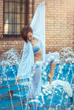 Dancer standing in the fountain. Girl dancer in the fountain makes pas Stock Images