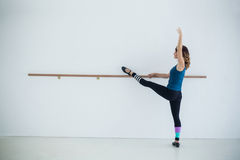 Dancer stretching on a barre while practicing dance Royalty Free Stock Image