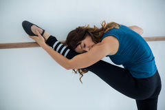 Dancer stretching on a barre while practicing dance Royalty Free Stock Images