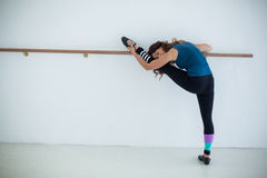 Dancer stretching on a barre while practicing dance Royalty Free Stock Photo