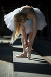 Dancer tying pointe shoes Royalty Free Stock Photos