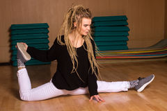 The dancer in white pants is sitting on a twine. In the dance studio Stock Image