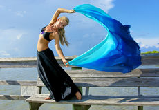 Dancer in the wind. A beautiful blonde fit and trim belly dancer strikes a dramatic pose as the wind blows he hair, skirt, and veil Royalty Free Stock Photo