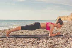 Dancer woman doing plank on the beach royalty free stock image