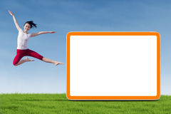 Dancer woman jumping with empty board. A young dancer woman jumping with empty board on the meadow Royalty Free Stock Image