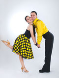 Dancers. Funny dancers in yellow clothing over grey background Royalty Free Stock Image