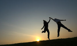 Dancers. Silhouetted teenager boy and girl dancing against the setting sun stock images