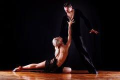 Dancers in ballroom. Against black background Stock Images