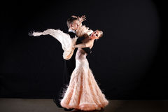 Dancers in ballroom against on black Stock Image