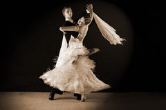 Dancers in ballroom against on black Stock Images